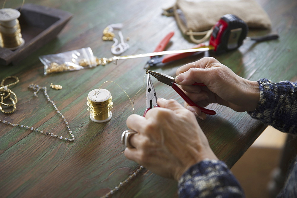 A tabletop with jewellery making equipment. Hands twisting wire on a necklace, New York, USA