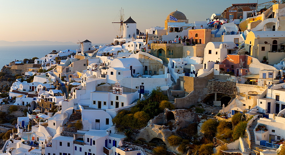 The windmills of Santorini in Greece. A hilltop town of whitewashed houses. Sunset, Aegean Sea, Greece