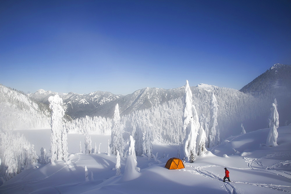 Michael Hanson walks through deep powder to his campsite in the snow covered Cascade Mountains overlooking Snow Lake, Cascade Mountains, Washington, USA