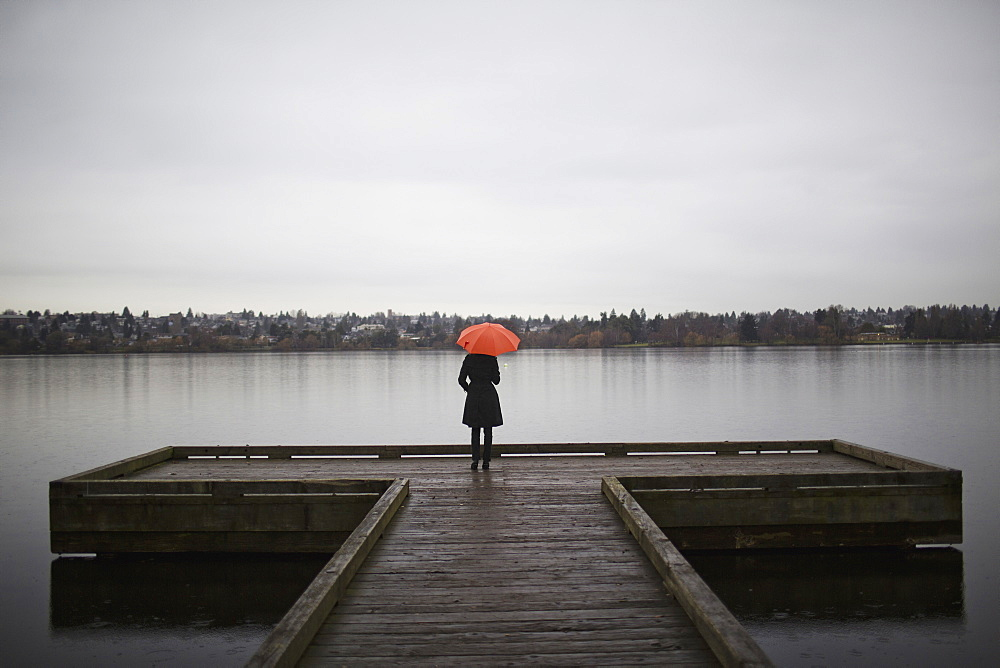 A woman wearing all black and holding an orange umbrella stands on the edge of a dock on a grey and cloudy day in Seattle, WA, Seattle, Washington, USA