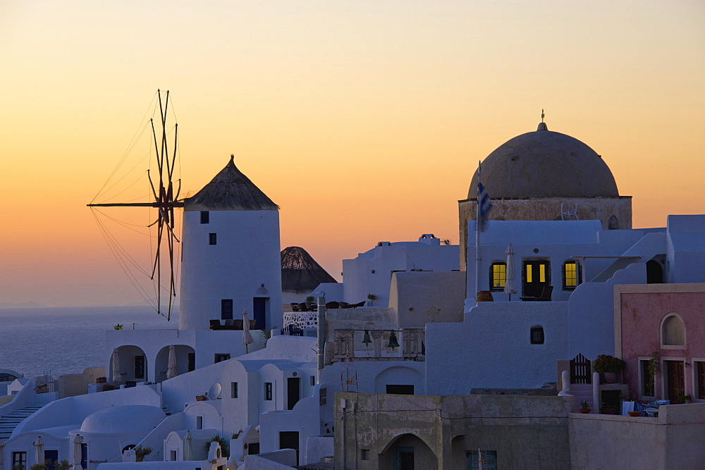 The historic white washed houses, windmills and domed church of Oia town on Santorini island, Oia, Santorini, Greece