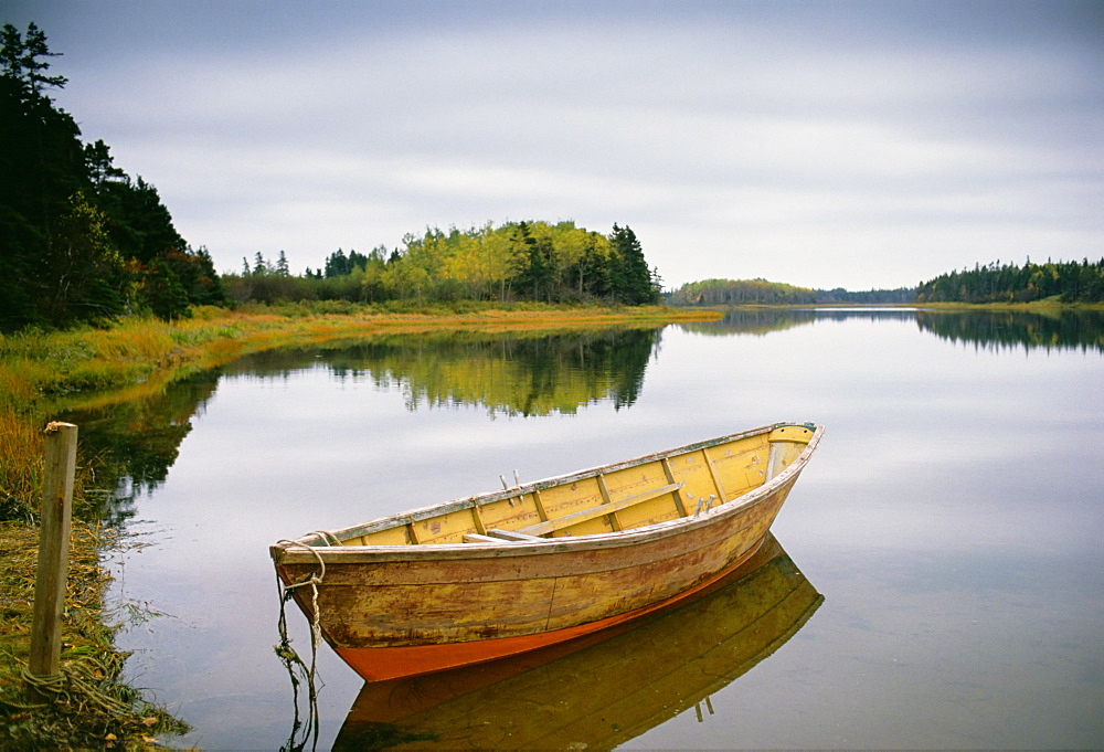 A small wooden dory or rowing boat moored on flat calm water, in Savage harbour on Prince Edward Island in Canada, Savage Harbor, Prince Edward Island, Canada