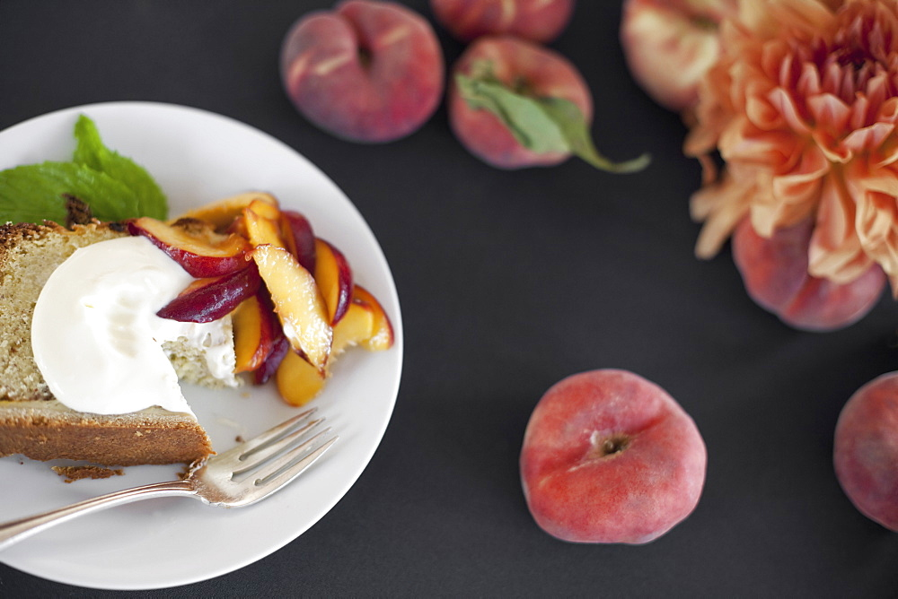A table viewed from overhead. Organic fruit, peaches, and flowers. a plate with fresh fruit, cake and creme fraiche. A fork. Dessert, Park City, Utah, USA