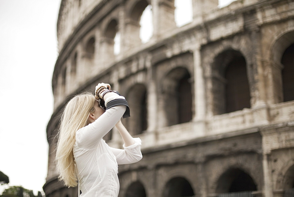 A woman outside the Colosseum amphitheatre in Rome, taking photographs, Rome, Italy