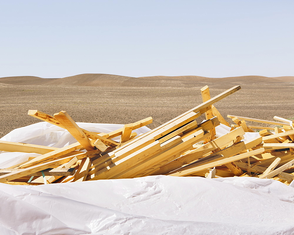White tarp covering pile of wood 2x4 studs, farmland in background, near Pullman, Pullman, Washington, USA