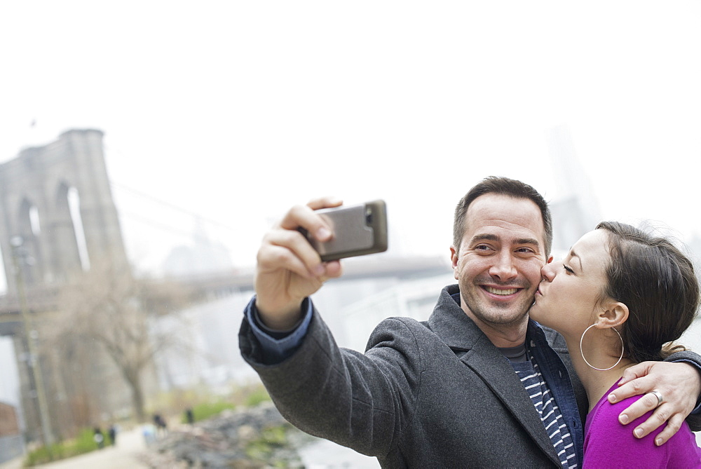New York city. The Brooklyn Bridge crossing over the East River. A couple taking a picture with a phone, a selfy of themselves, New York city, USA