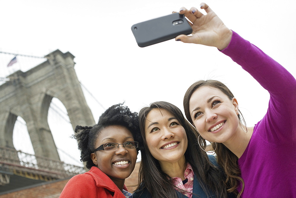 New York city, the Brooklyn Bridge crossing over the East River. Three women in a row, smiling, as one takes a picture with a smart phone, New York city, USA