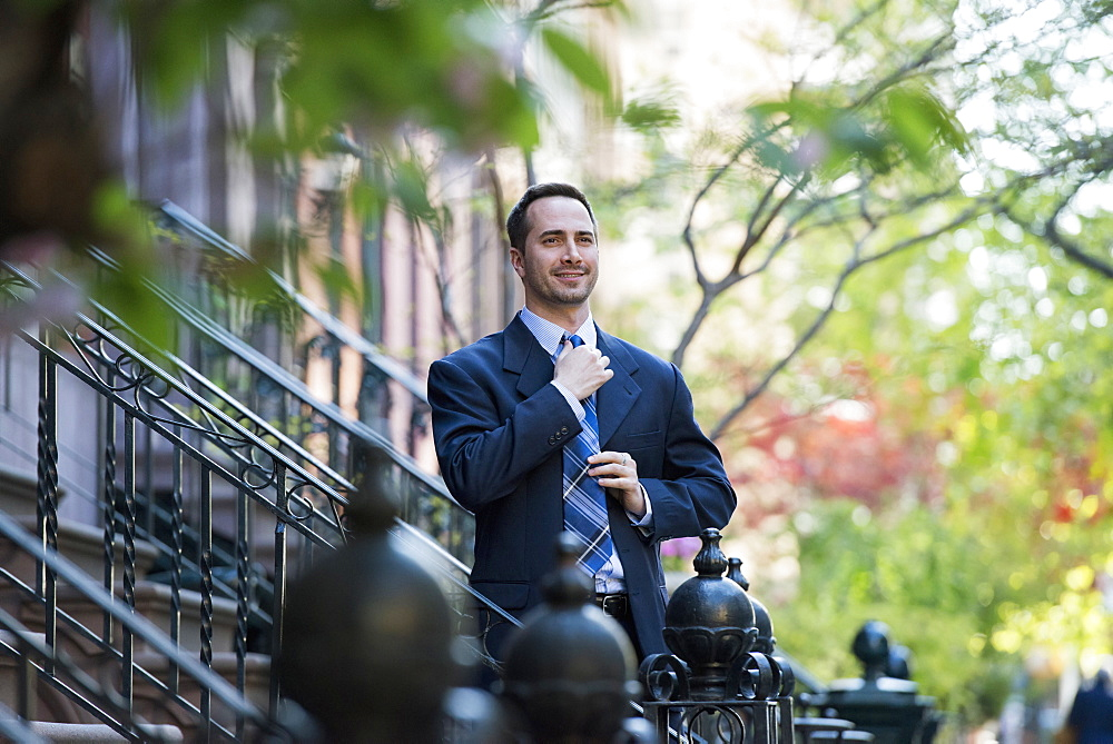 A man in a business suit adjusting his tie. At the bottom of the steps of a townhouse in a terrace.