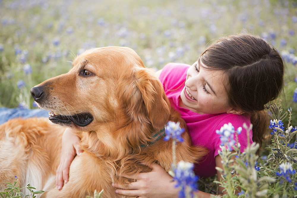A young girl hugging a golden retriever pet, Girl, Texas, USA