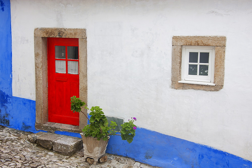 A red painted door of an old house in a street in Sonega, Sonega, Portugal