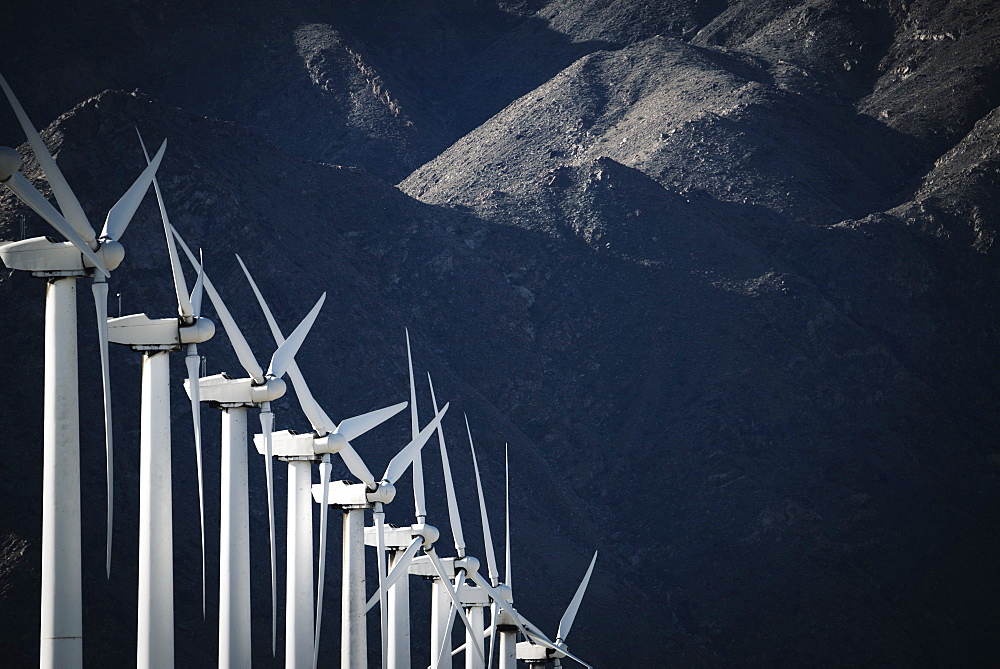 White wind turbines, in a row, against the backdrop of a snow capped mountain, California, USA