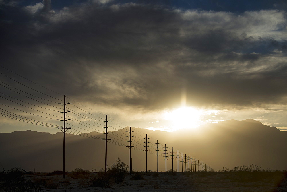Power lines in rows across the landscape, against a darkening sky, California, USA