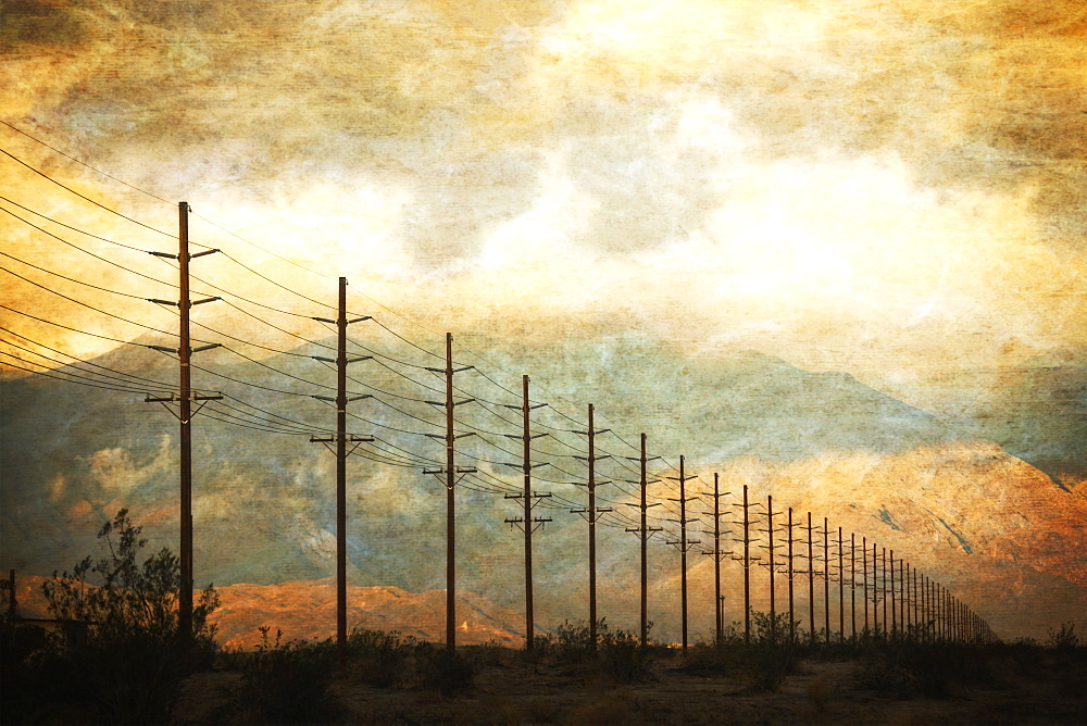 Power lines in rows across the landscape, against a sunset sky, California, USA