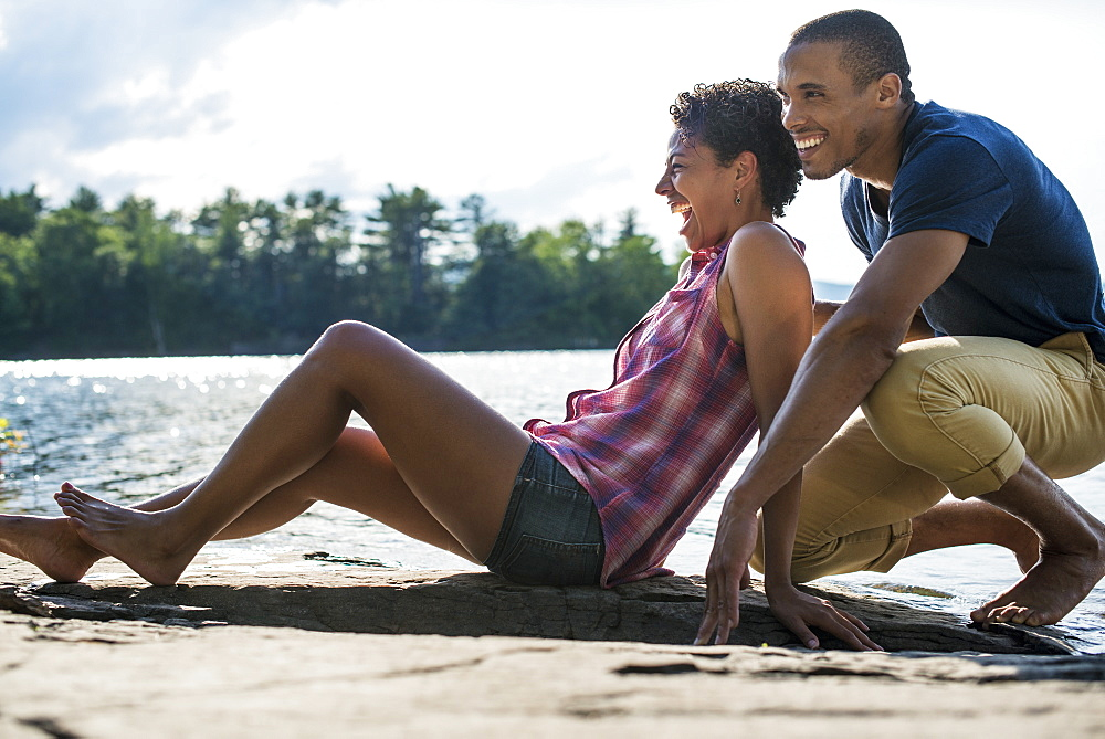 A couple close together by a lake in summer