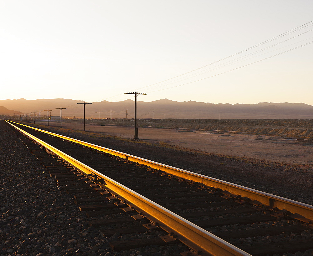 Railroad tracks extending across the flat Utah desert landscape, at dusk, Tooele County, Utah, USA