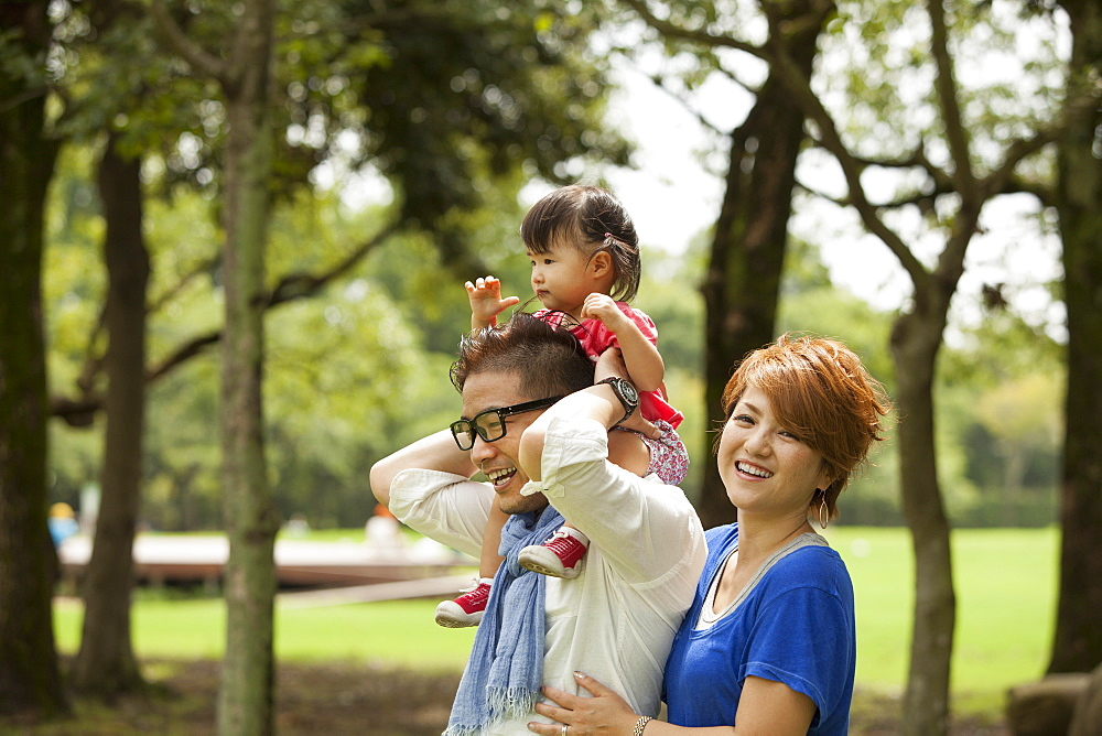 Family in a park. Two parents and a toddler, Kyoto, Honshu Island, Japan