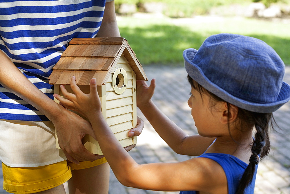 Young girl wearing a summer dress and sun hat, holding a bird house, Kyoto, Honshu Island, Japan
