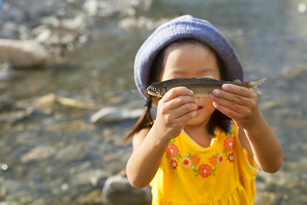 Young girl wearing a summer hat, holding a fish, Kyoto, Honshu Island, Japan