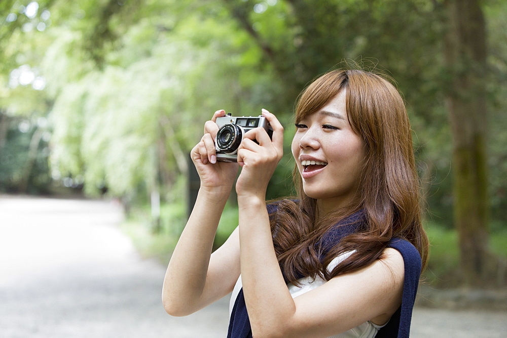 A woman in a Kyoto park holding a camera, Kyoto, Honshu Island, Japan
