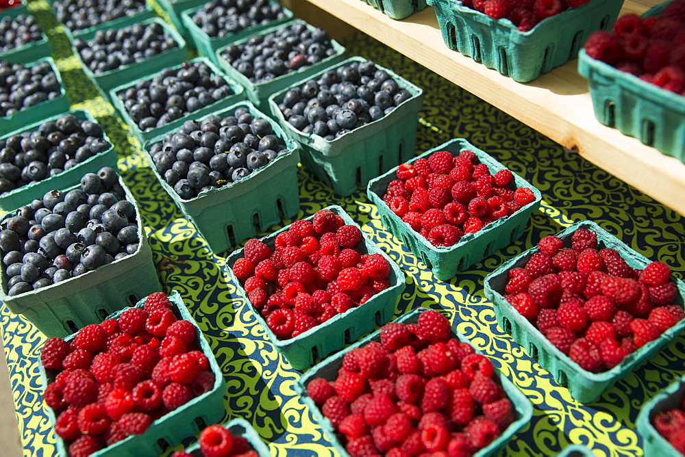 A farm stand, with displays of punnets of fresh berry fruits. Raspberries and blueberries, Woodstock, New York, USA