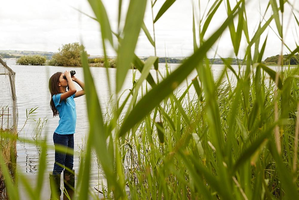 A young girl, a birdwatcher with binoculars, Bristol, Avon, England