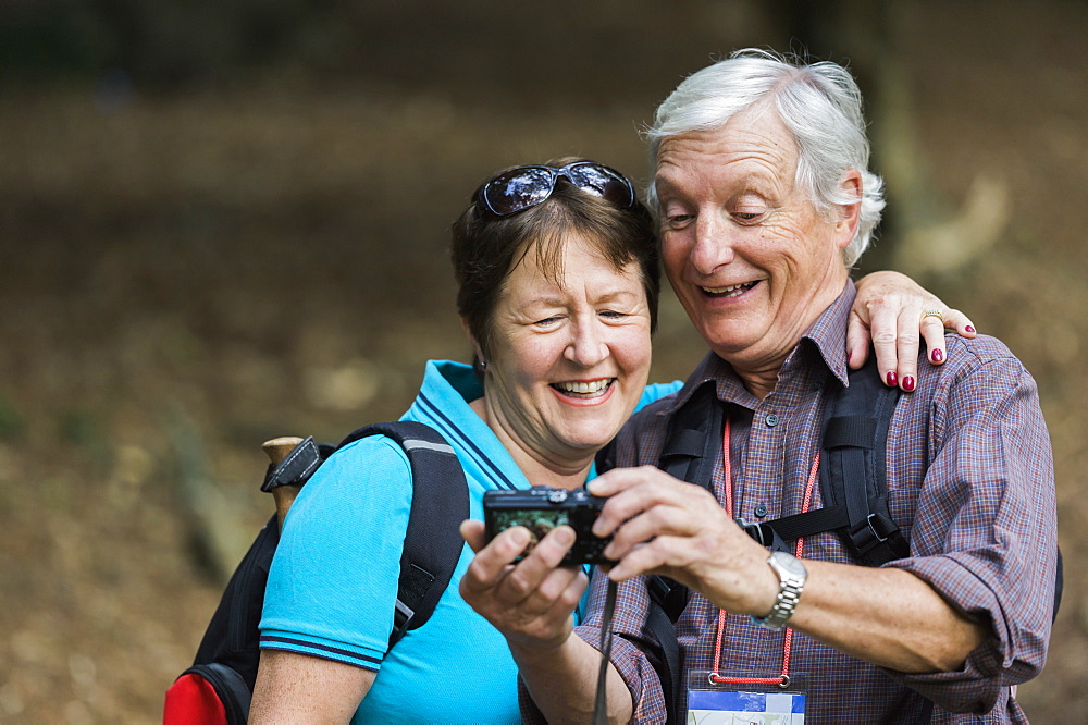 A mature couple looking at a digital camera, laughing, England
