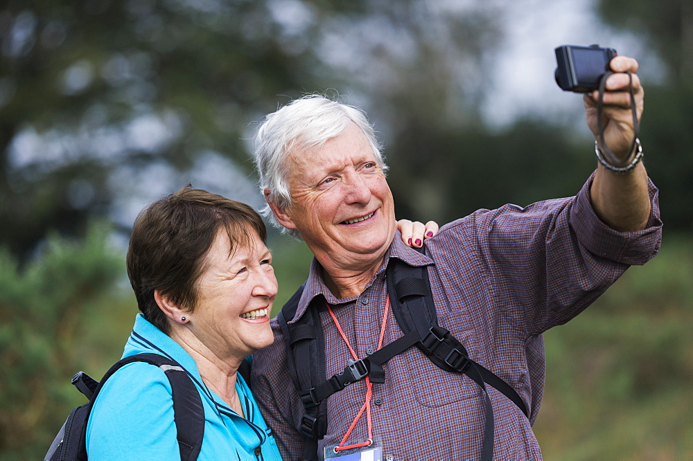 A mature couple taking a selfy photograph while out walking, England
