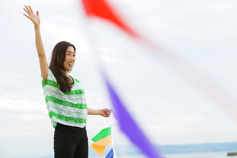 A woman on a beach in Kobe holding paper flags, Kobe, Japan