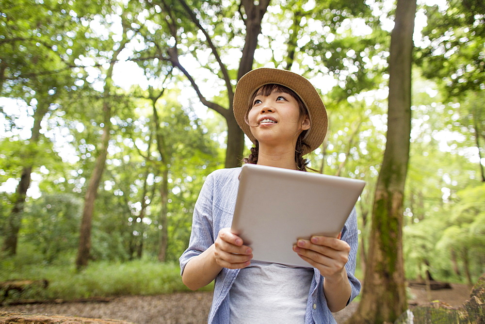 Young woman holding a digital tablet in a forest, Kyoto, Japan
