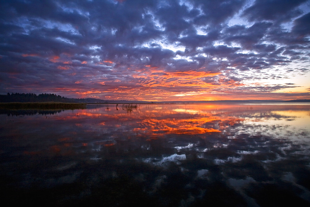 Sunset sky reflected in a lake, and clouds in the skySunset, Saskatchewan, Canada
