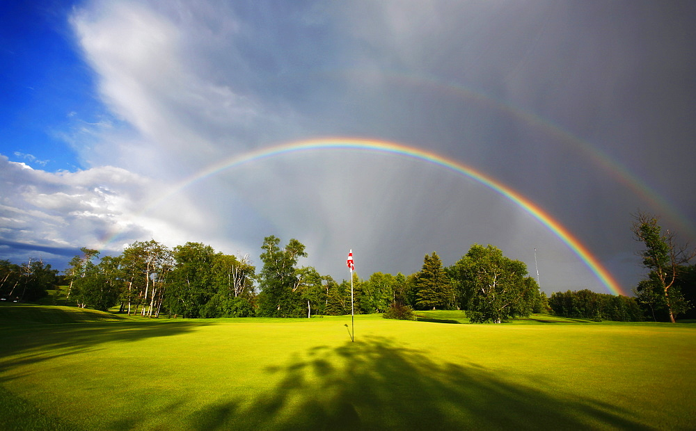 A rainbow in the sky above a golf greenGolf course, Saskatchewan, Canada