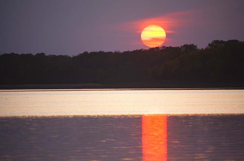 An orange sun sinking below the horizon, reflected in the water of a lakeLake sunset, Saskatchewan, Canada
