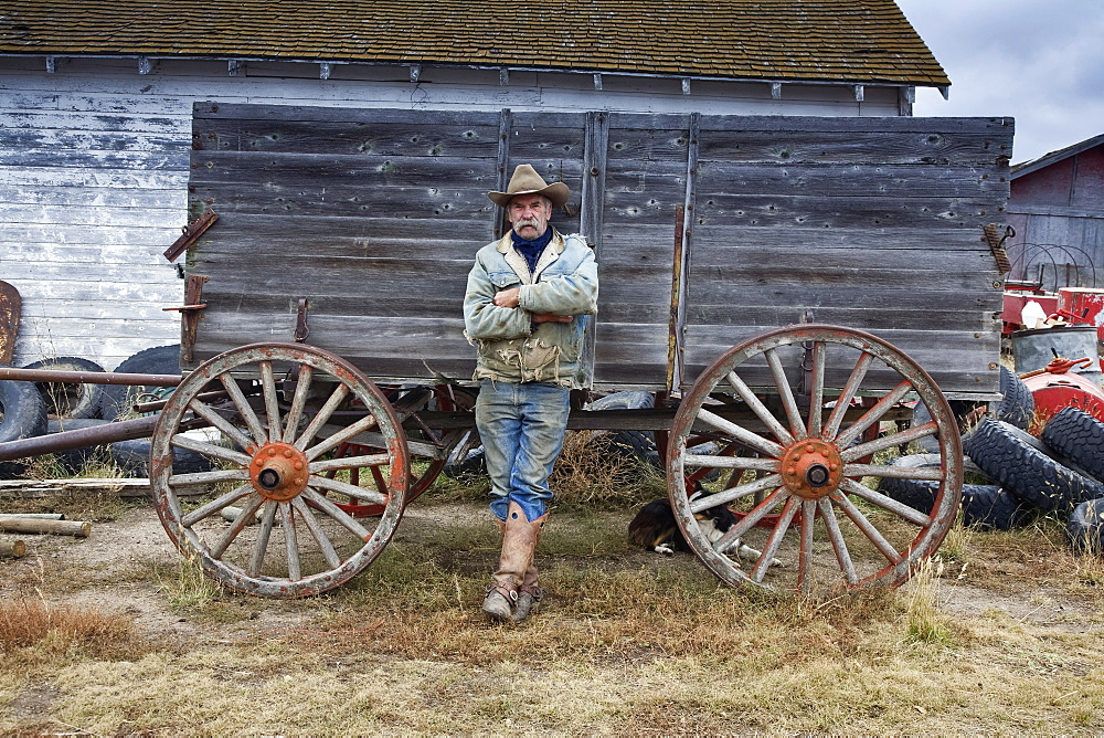 Man in cowboy hat and cowboy boots leaning against a wooden wagonCowboy, Saskatchewan, Canada