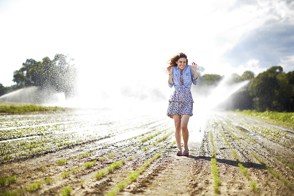A young woman in denim jacket standing in a field, irrigation sprinklers working in the background, New York State, USA