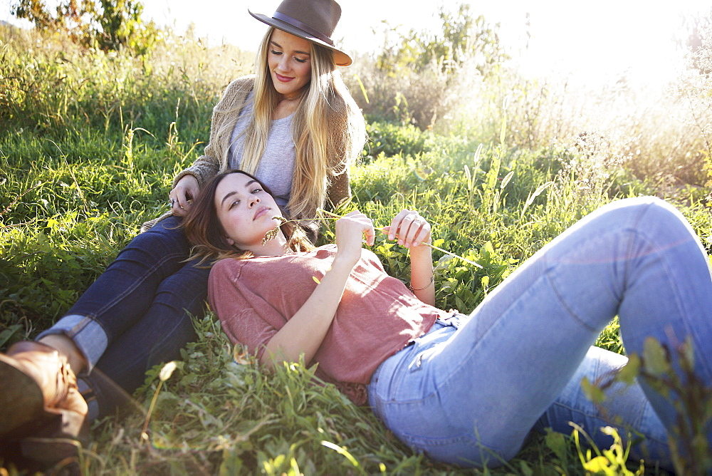An apple orchard in Utah. Two women lying in the grass, Sataquin, Utah, United States of America