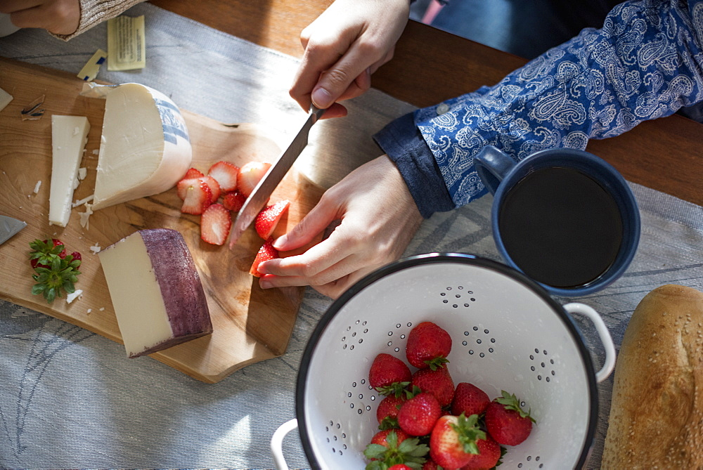 A woman slicing strawberries on a table with a wooden chopping board with a selection of cheeses and bread, Woodstock, New York State, USA
