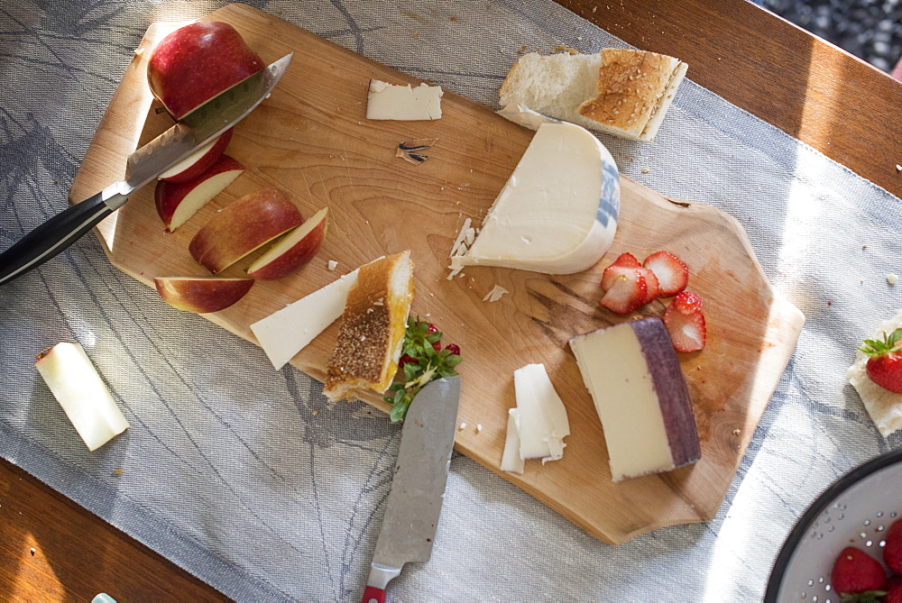 Knives and a wooden chopping board with a selection of cheeses, apples and bread, Woodstock, New York State, USA