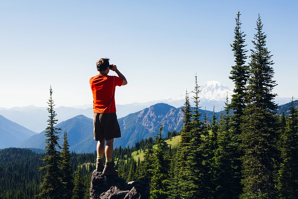 A man standing on a mountain ridge, taking a photograph of the landscape, Skamania County, Washington, USA