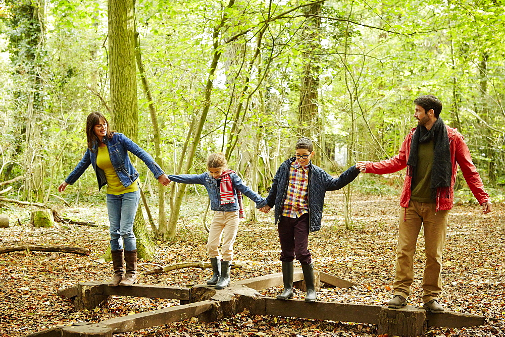 Beech woods in Autumn. A family of four people, two adults and two children, England, United Kingdom