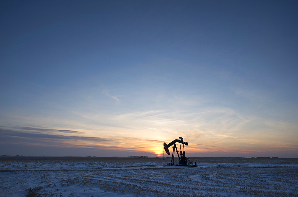 An oil drilling rig and pumpjack on a flat plain in the Canadian oil fields at sunset, Canada