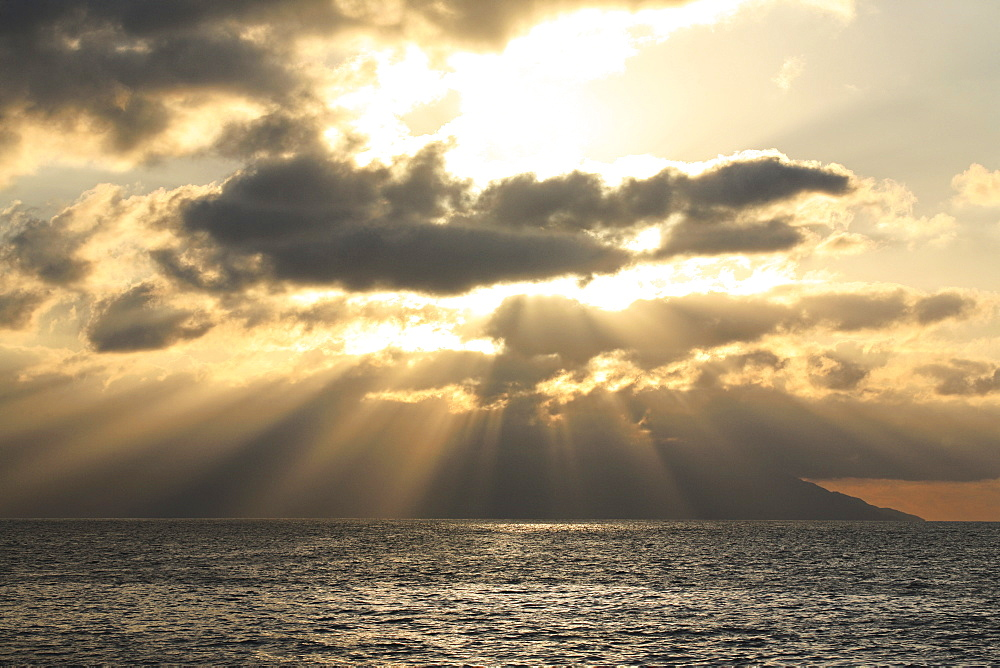 Sunset over the ocean, shafts of sunlight falling to the water, and layers of clouds, Mexico