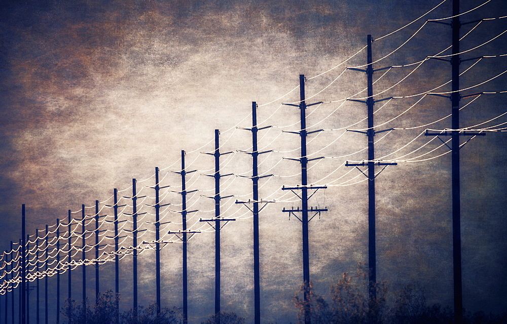Power lines at regular intervals reaching into the distance against a patch of clearing sky and cloud, United States of America