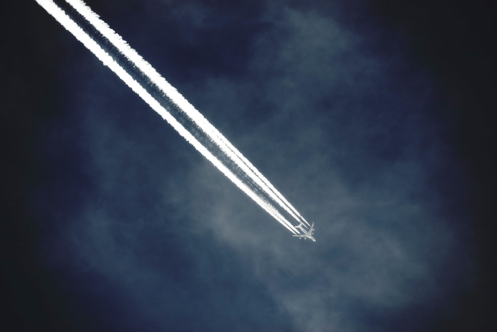 A jet with a clear condensation or vapour trail or contrail across a dark blue sky