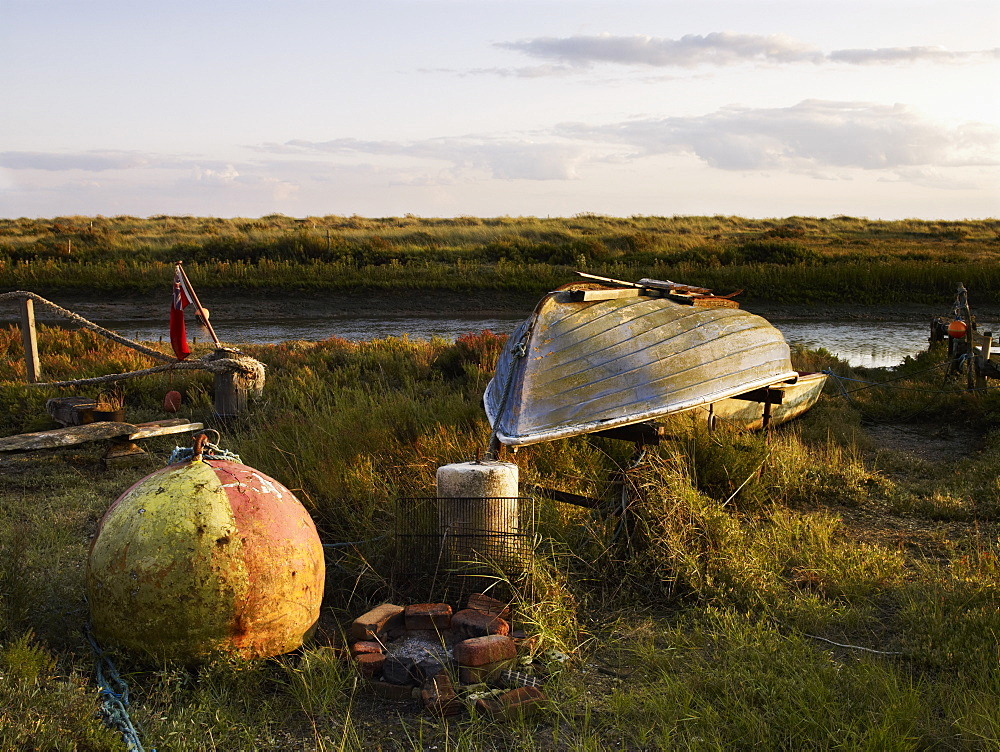 An upturned fishing boat by a narrow water channel in a flat landscape. Fishing floats and buoys, Fishing boat, England