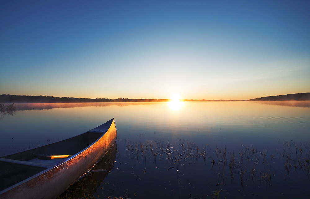 A canoe on a flat calm lake at sunset, Kenosee Lake, Saskatchewan, Canada