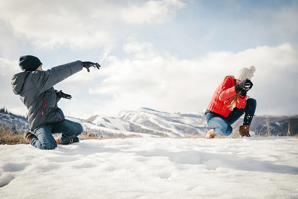 A snowball fight between a brother and sister, Mountains, Utah, USA