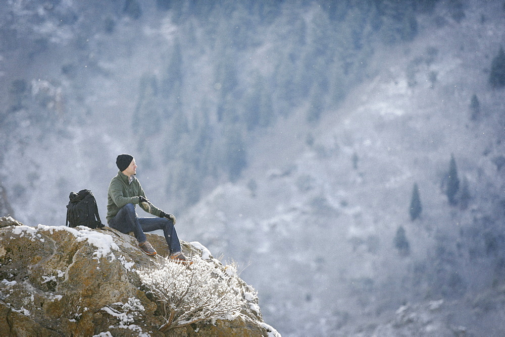 A man, a hiker in the mountains, taking a rest on a rock outcrop above a valley, Mountains, Utah, USA