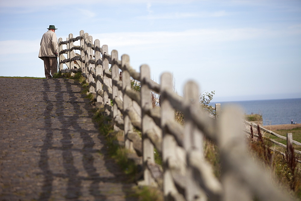 An elderly man standing on the seafront walkway looking out to sea, Sea coast, Northumberland, England