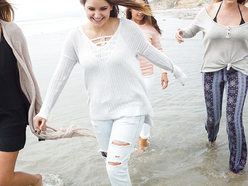 A group of smiling young women walking on a beach.