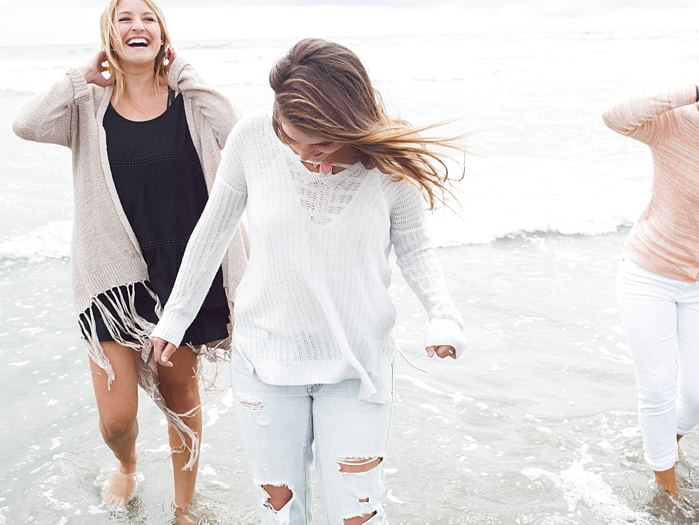Three smiling young women walking on a beach.